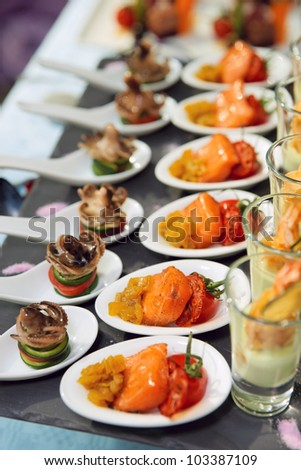 Spoons with seafood snacks on restaurant table - stock photo