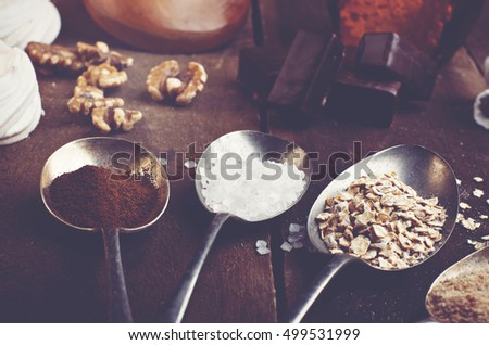 Spoons with sugar, coffee, oats and meringue, chocolate marshmallow, honey and nuts on a real brown wooden table.