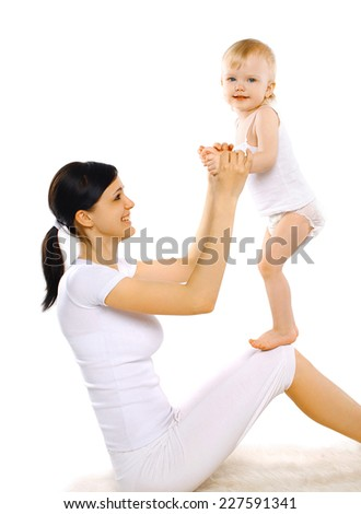 Sport, active, leisure and family concept - happy mom and baby doing exercise having fun - stock photo