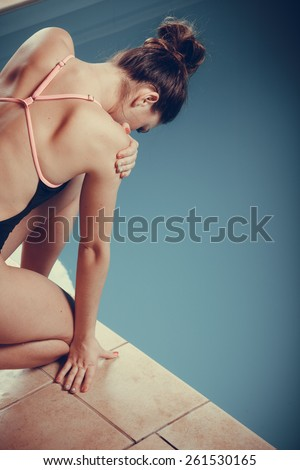 Sport active lifestyle. Sporty woman female swimmer muscular fit body preparing to jumping and diving into swimming pool sideview - stock photo
