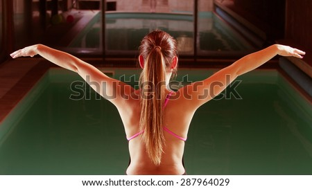 Sport active lifestyle. Sporty woman female swimmer muscular fit body preparing to jumping and diving into swimming pool  back view - stock photo