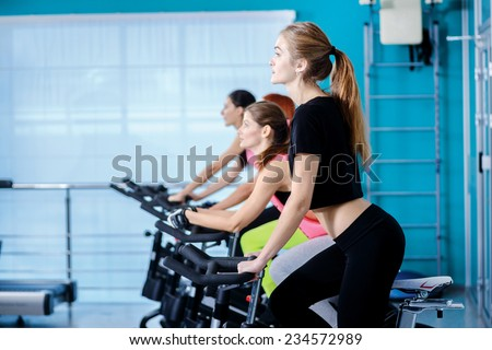 Sport activities on bicycles. Girl pedaling on the simulator until her four girlfriends athletes pedaling on a stationary bike at the gym. - stock photo