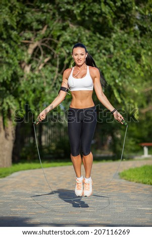 Sport, activity. Cute woman with skipping rope - stock photo