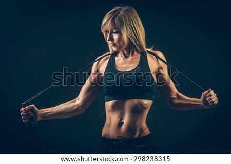 Sport, activity. Cute woman with skipping rope. Muscular woman  black background. - stock photo