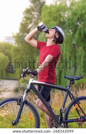 Sport and Cycling Concept: Young Caucasian Male Cyclist Having water Break Outdoors and Holding Mounting Bike. Vertical Image Composition - stock photo