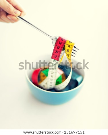 sport and diet concept - woman hand with fork, bowl and measuring tape - stock photo