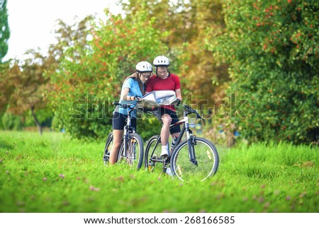 Sport and Fitness Concept. Happy caucasian Couple of Cyclists With Location Map Outdoors.Horizontal Image Composition - stock photo