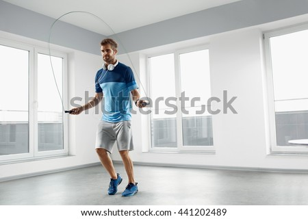 Sport And Fitness Workout. Healthy Athletic Man With Muscular Body In Fashion Headphones, Sportswear Skipping With Jump Rope, Exercising Indoor. Handsome Male Doing Jumping Cardio Exercise Training. - stock photo