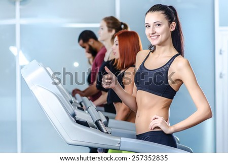 Sport and healthy fitness life. Sport and slender girl running on a treadmill and looking at the camera and showing thumb up. Athlete dressed in sports uniforms and running in the gym. - stock photo