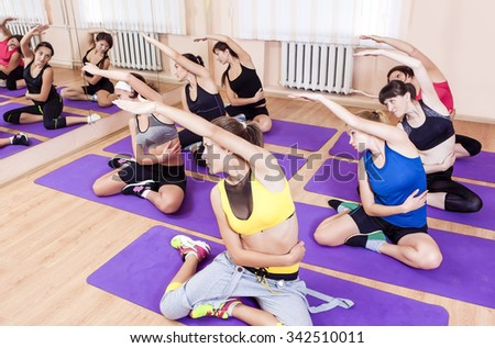 Sport and Healthy Life Concepts. Group of Seven Young Caucasian Females Having Fitness Class in Sport Club and Stretching.Horizontal Image Orientation - stock photo