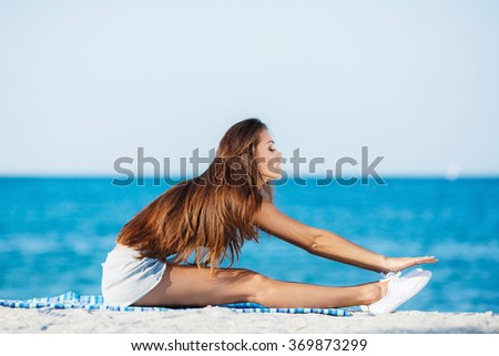 sport and lifestyle concept - woman doing sports by sea. Beautiful teenage sport woman doing stretching exercise on sand beach. Yoga. beautiful young brunette woman smiling and listening to music  - stock photo