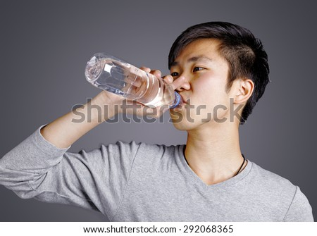Sport asian man drinking water on blackground