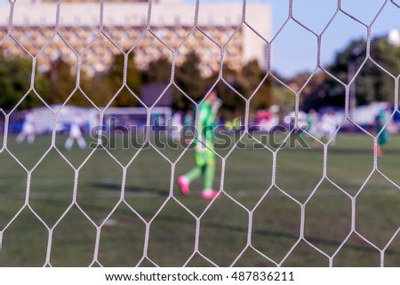 Sport background blur. Boke spectacular game football as background for sports poster. look at blurred soccer field with goalkeeper through net. blurred background without focus for screen background