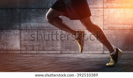 Sport background, close up of urban runner's legs run on the street with copy space - stock photo