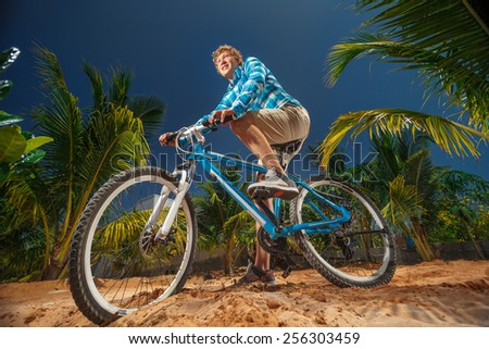 Sport bike cyclist doing extreme biking on the palm trees background - stock photo