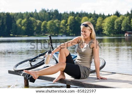 Sport biking young woman sitting on pier by natural lake - stock photo