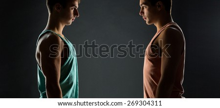 sport, bodybuilding, competition and people concept - young men looking to each other