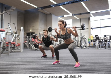 sport, bodybuilding, lifestyle and people concept - young man and woman with barbell flexing muscles and making shoulder press squat in gym - stock photo