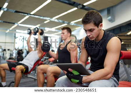 sport, bodybuilding, lifestyle, technology and people concept - group of men with tablet pc computer flexing muscles in gym - stock photo