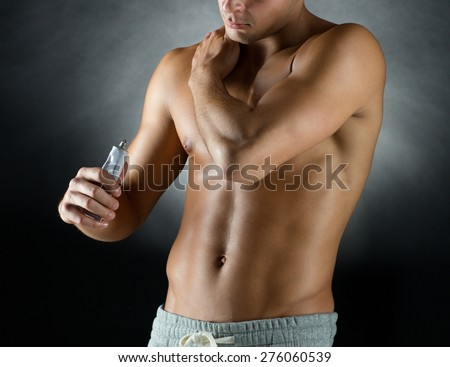 sport, bodybuilding, medicine and people concept - young man standing over black background and applying pain relief gel on his shoulder - stock photo