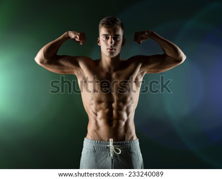 sport, bodybuilding, strength and people concept - young man showing biceps and muscles over dark background - stock photo