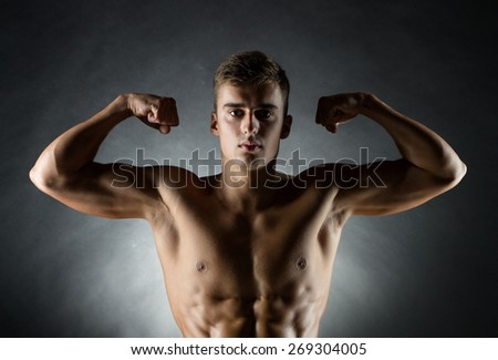 sport, bodybuilding, strength and people concept - young man showing biceps over black background - stock photo