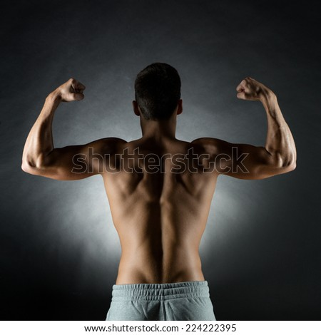 sport, bodybuilding, strength and people concept - young man showing biceps over gray background from back - stock photo