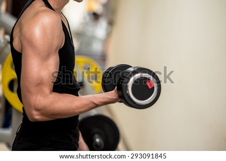 sport, bodybuilding, training and people concept , young man with dumbbell flexing muscles in Fitness Room. - stock photo