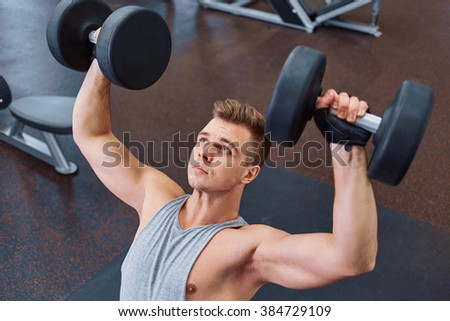 sport, bodybuilding, training and people concept - young man with dumbbell flexing muscles. men working with dumbbells his body at gym.