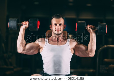 sport, bodybuilding, weightlifting, lifestyle and people concept - young man with dumbbells flexing muscles in gym - stock photo