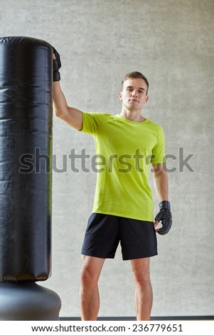 sport, box and people concept - young man with boxing gloves and punching bag in gym - stock photo