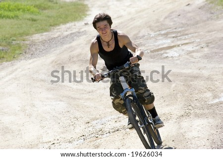 Sport build teenager ride by bicycle in summer day at vacation - stock photo