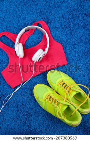 Sport clothes, shoes and headphones on color carpet background.  - stock photo