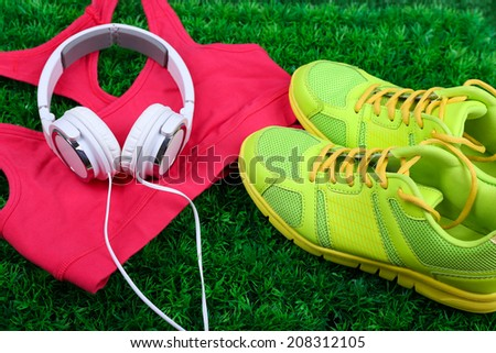 Sport clothes, shoes and headphones on green grass background - stock photo
