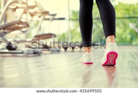 Sport concept. Close up of female feet in sneakers in gym. - stock photo