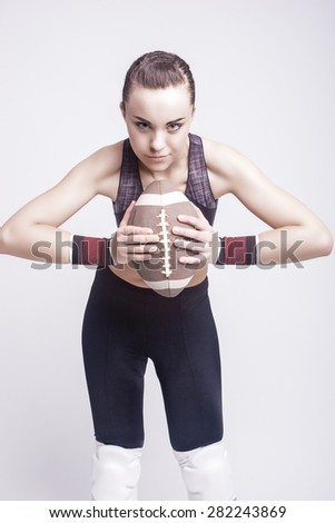 Sport Concept: Sportive Caucasian Female American Football Player with Ball. Vertical Image - stock photo