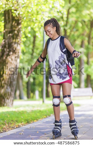 Sport Concepts. Young African American Teenage Girl Learning Roller Skating in Park Area. Vertical Image