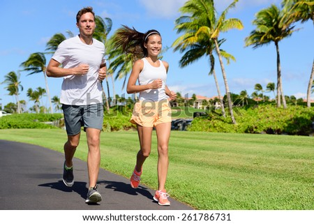 Sport couple exercising running outside on street in summer. Happy active young fit adults jogging together with tropical background in city park or resort road. Asian and Caucasian people. - stock photo