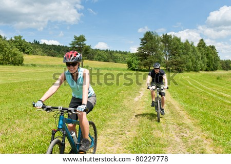 Sport couple riding mountain bicycles in countryside meadows
