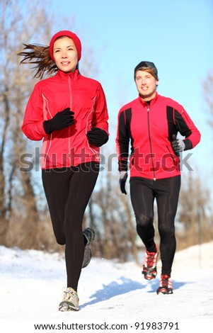 Sport couple running in winter snow. Woman and man runners jogging outdoors. Healthy fitness lifestyle concept with happy smiling young multiracial couple. - stock photo