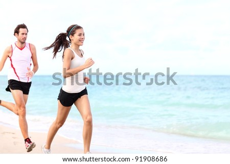 sport - couple running on beach training for marathon run. Young multiracial couple runners, smiling asian female fitness model and caucasian male model. - stock photo