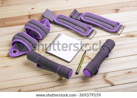 Dumbbells Ankle Weights Wrist And Notebook To Workout Plan On