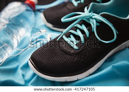 Sport equipment. Sneakers, bottle with water, sportswear. - stock photo