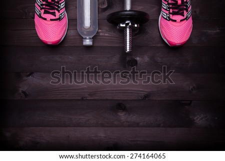 Sport equipment. Sneakers, water and a dumbbell on a black wooden background - stock photo