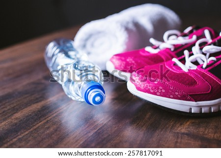 Sport equipment. Sneakers, water and towel on wooden background - stock photo