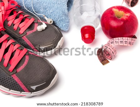 Sport equipment. Sneakers, water, earphones and apple, isolated on white background - stock photo