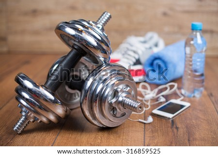 Sport equipment. Sneakers, water towel and earphones on wooden background. Sport fitness background