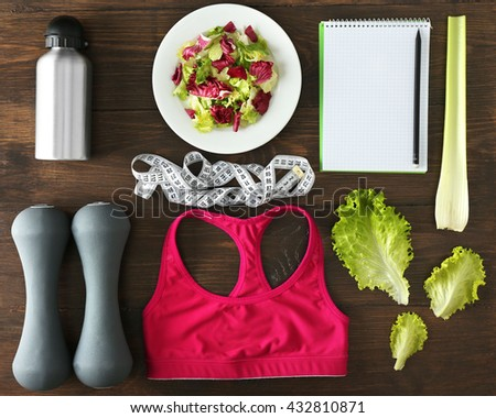 Sport equipment with female clothing and vegetables on wooden background - stock photo