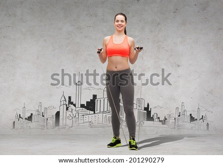 sport, exercise and healthcare - sporty woman with skipping rope with city drawing on the back - stock photo