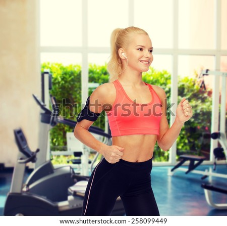 sport, exercise, technology, internet and healthcare - smiling sporty woman running and listening to music from smartphone - stock photo